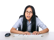 That's just so wrong. A girl looking very disturbed while sitting at a computer desk using a keyboard Royalty Free Stock Image