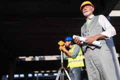 S?kert lag av arkitekter och teknikerer som tillsammans arbetar p? konstruktionsplats fotografering för bildbyråer
