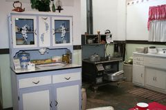 1940s kitchen. Museum display of a 1940s kitchen including a counter, cupboards, stove, sink, window and curtains plus dishes and decor. Cooking and baking pans Royalty Free Stock Photography