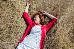 50s kobieta cieszy się słońca ciepło śpi pokojowo na suchej trawie Fotografia Stock