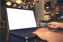 S kobiety ` ręki używać laptop z pustym białym desktop ekranem w kawiarni podczas gdy pijący gorącą kawę na drewnianym stole zdjęcie stock