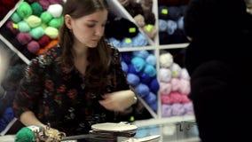 S?ljaren f?r den unga kvinnan p? det litet shoppar av hantverk arkivfilmer