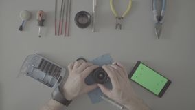 S-log. Male hands repair lens on grey table. S-log. Top view. Male hands scrolling a smartphone with green screen. Male hands repair photo lens on grey table stock footage