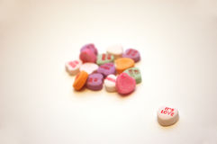 It's Love Valentine's Day Conversation Hearts. Colorful Valentine's Day conversation hearts with a white It's Love heart in the foreground stock images