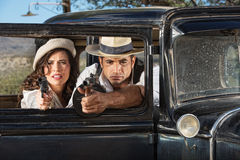 1920s Male and Female Gangsters. 1920s vintage gangsters firing guns from car window Royalty Free Stock Photography