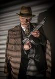 1940s male gangster holding a machine gun Stock Photo