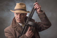 1940s male gangster holding a machine gun Stock Images