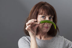 50s malheureux mûrissent la femme remettant en cause le goût du poivron vert Photos stock