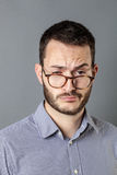 30s man looking sleepy, indifferent and careless with eyeglasses down. Portrait of tired 30s man looking sleepy, indifferent and careless with eyeglasses down Royalty Free Stock Image