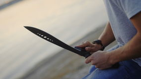 20s man sharpening his machete in the evening sitting on the shore of the bay. stock video