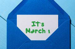 It`s March - Note in letter at blue envelope. Spring beginning concept. It`s March - Note in letter at blue envelope. Spring beginning Stock Photo