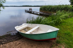 渔夫` s小船和桥梁有结尾杆的在Masuria湖, 免版税库存照片