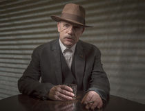 1940s mature male gangster having a drink. On a grey background stock image