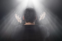 It's a miracle! Rear view of man standing in front of the window. With his hands raised up stock photos