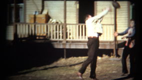 (1950's 8mm Vintage) Guys Playing Football in Front Yard in Dress Clothes stock video footage