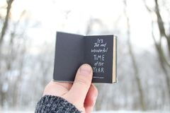 It`s the most wonderful time of the year. Hand holding a book with text on background - snowy winter park Royalty Free Stock Photos
