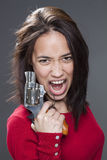 20s multi-ethnic woman screaming, holding handgun. Female power concept - enraged 20s multi-ethnic woman screaming in holding a handgun for revenge against royalty free stock photography