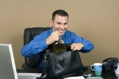 It's my tea!. Employee smuggling some whiskey at his office in the working hours, happy about being able to pass through unnoticed Stock Photography