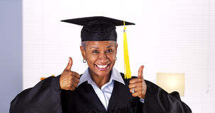 It's never too late to graduate. Enthusiastic mature black woman in graduation gown Royalty Free Stock Images