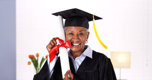 It's never too late to graduate. Enthusiastic mature black woman in graduation gown Stock Image