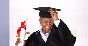 It's never too late to graduate. Enthusiastic mature black woman in graduation gown Royalty Free Stock Photo