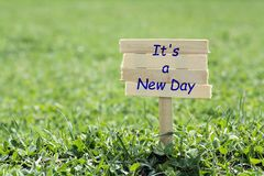 It`s a new day. Wooden sign in grass,blur background stock photo