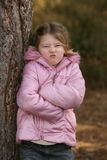It's not fair!. A young girl leaning against a tree pulling a face and folding her arms Royalty Free Stock Images