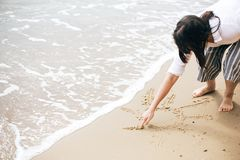 S?o?ce znak na pla?y Dziewczyna pisze s?o?ce symbolu tekscie na piaskowatej pla?y przy dennymi falami Cze?? lata poj?cie Wakacje, zdjęcie royalty free