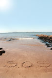S o s. Sos inscribed on the beach with waves in the background on a hot sunny day stock photography