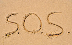 S.O.S. SOS word written in the sand on the beach Stock Photos