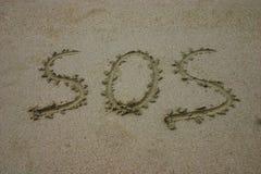 S.O.S. dat in zand wordt geschreven Stock Foto