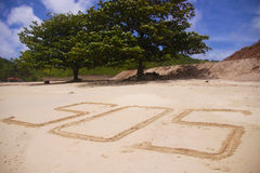 S.O.S on the sand;. Pretty big text S.O.S on the sand. Two trees and blue sky on the background Stock Photos