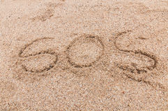 S.O.S written in the sand. With a finger or stick Stock Images