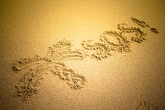 S.O.S written in the sand.Beach background. Top view. tinted Stock Photography