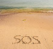 S.O.S written in the sand. With a finger or stick Royalty Free Stock Photo