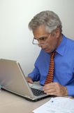 That's odd!. A mature businessman sits in front of his laptop computer, looking at the screen inmild surprise. Space for text on the white background Stock Image