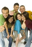 That's OK!. Group of 6 happy teenagers. They're showing thumb up hand sign to the camera. Wide angle. White background Stock Photos