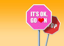 It's OK, Go On. Pink traffic sign saying It's OK, Go On, in front of regular red STOP sign Stock Image