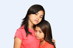 It's okay sis!. A teenager girl trying to comfort her younger sister with a hug & sad eyes royalty free stock images