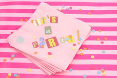 It's a party. Cut out letters spelling it's a party on pink napkins with curled ribbons and confetti, great for invitation cards Royalty Free Stock Image