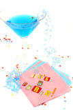 It's a party. Spelled out with cut out letters on blue napkin with blue martini with confetti and curled ribbons great for party invitations Stock Photo