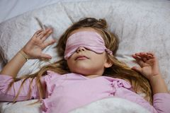 She`s a peaceful princess. Little girl sleeping in bed. Close up stock photo
