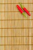 S/poivron rouges sur un couvre-tapis en bambou Photo libre de droits