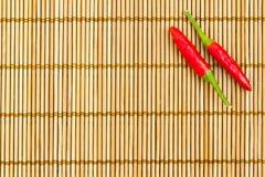 S/poivron rouges sur un couvre-tapis en bambou Photo stock