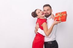 It`s present for you! Couple hugging, woman holding gift box. It`s present for you! Couple hugging, women holding gift box. Indoor, studio shot, on gray royalty free stock photo
