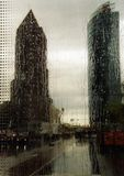 It´s raining in Berlin. This is a view through a pane of a bus stop, while it was raining. You can see two high-rise buildings of the Potsdam´s place in Stock Photography