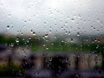 It's a raining day. Raining in the yard. Water drops on the window royalty free stock image