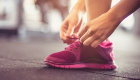 She`s always ready. Sportswoman tying sneakers and preparation for exercise. Close up. Space for copy royalty free stock photo