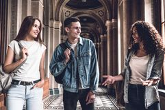 It `s Real emotions. Three Beautiful students are walking in the university ,chatting and smiling.  stock image