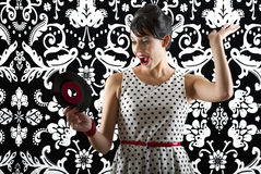It's a record. Young woman in front of a black and white textured background with 60's inspired style, holding a small record with a red label Royalty Free Stock Images